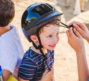Camper getting help with his helmet