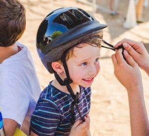 Camper getting their helmet adjusted