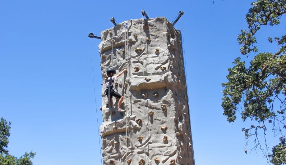 Camper climbing the rock climbing wall