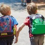 Two boys walk with backpacks