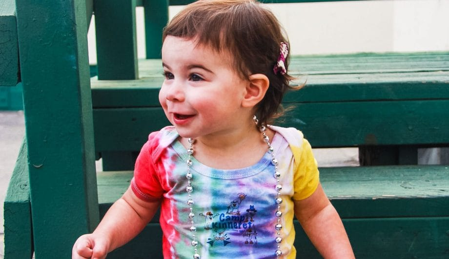 Toddler in Camp Kinneret Tie Dye Onsie