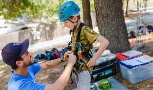 Staff helping camper get on his rock climbing gear