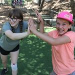 Two campers give double high fives